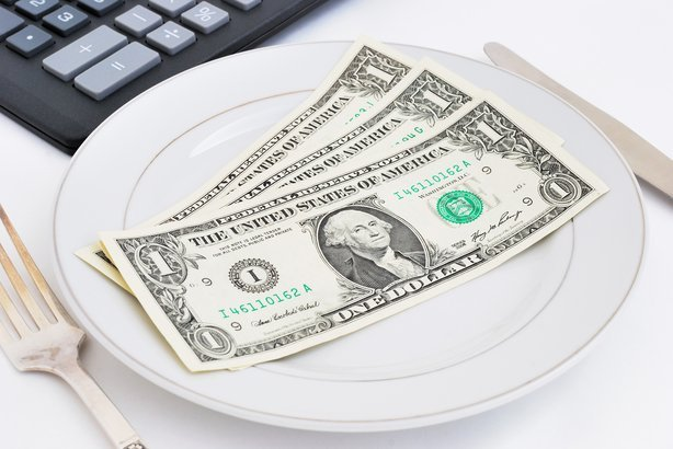three dollars on plate with calculator in the background