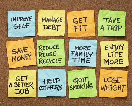 several popular new year resolutions on colorful sticky notes on a cork board