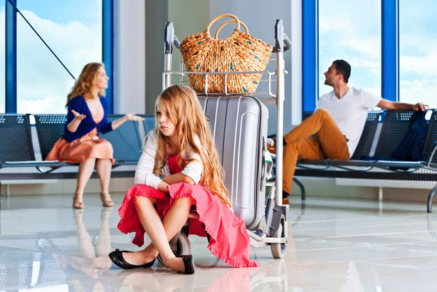 couple having argument at the airport with moody kid sitting with luggage