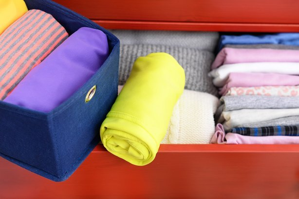 neatly folded clothes in open drawer