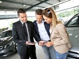 couple in car dealership looking at brochure with salesman