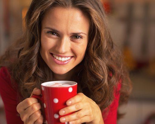 smiling woman in christmas red dress having cup of hot chocolate with marshmallow