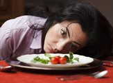 woman looking at three tomatoes on plate