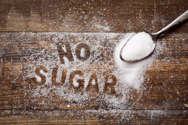text no sugar written with sugar on wooden board