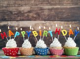 birthday cupcakes with 'Happy Birthday' in candles