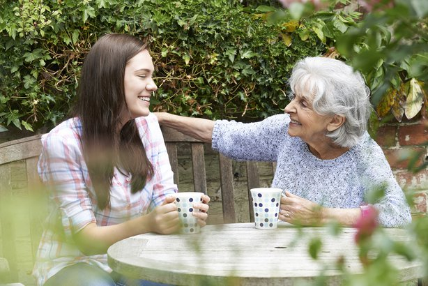 young adult granddaughter relaxing with grandmother in garden
