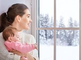 mother and baby hugging near window with snow outside