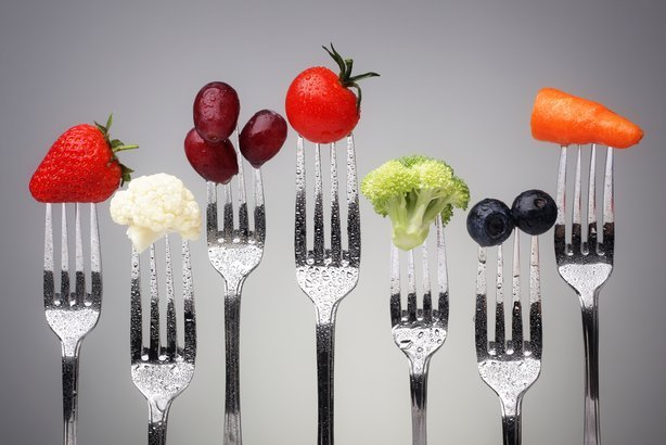fruit and vegetable of silver forks against a grey background