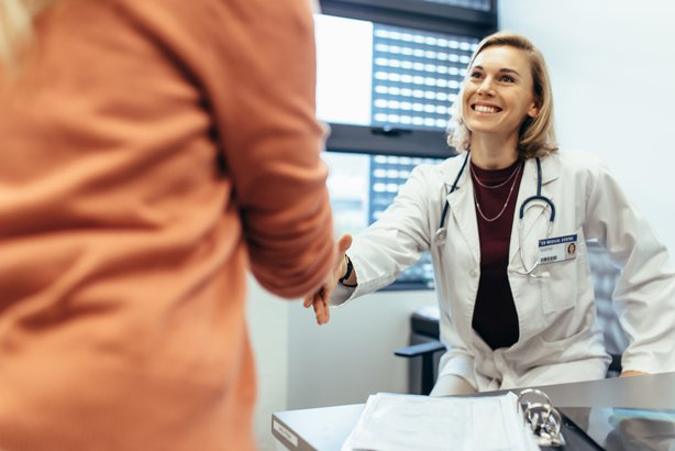 smiling medical doctor shaking hands with patient