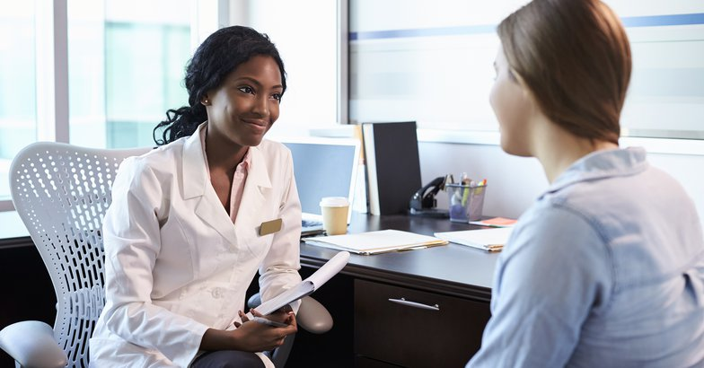 African American doctor in consultation with female patient in office