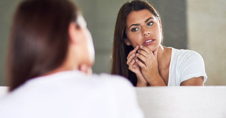 woman in mirror looking at pimple