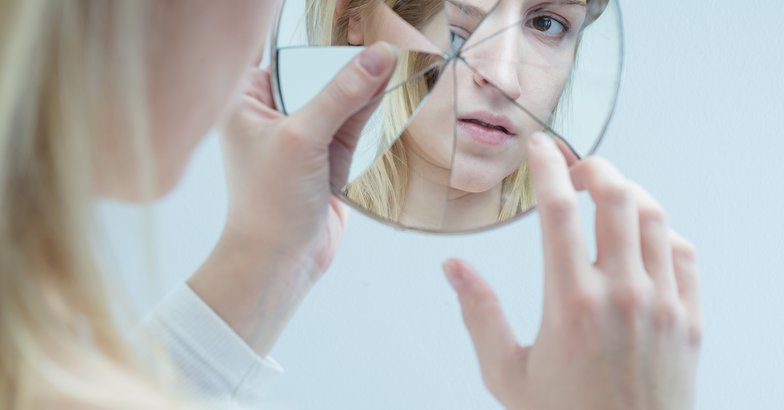 woman looking at herself in broken looking glass