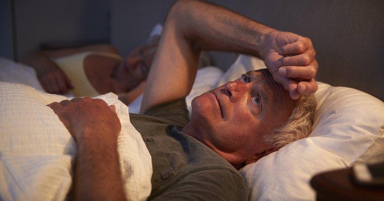 worried man in bed near his sleeping wife