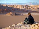 tourist sat on rock looking Valle de la Luna, Chile