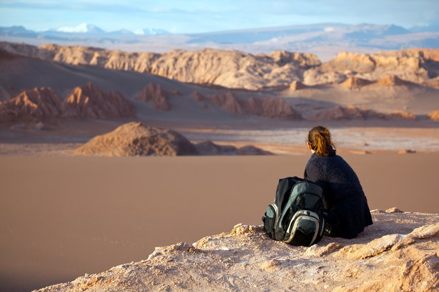 tourist sat on rock looking Valle de la Luna, Chile