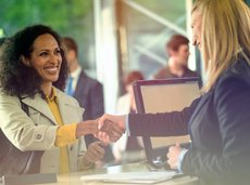 African American woman shaking hands with bank worker
