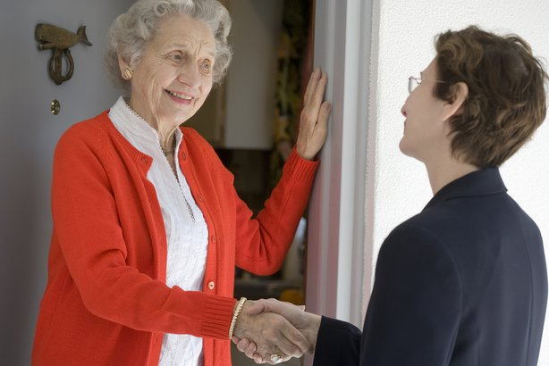 middle-aged woman shaking hand of senior woman at her front door