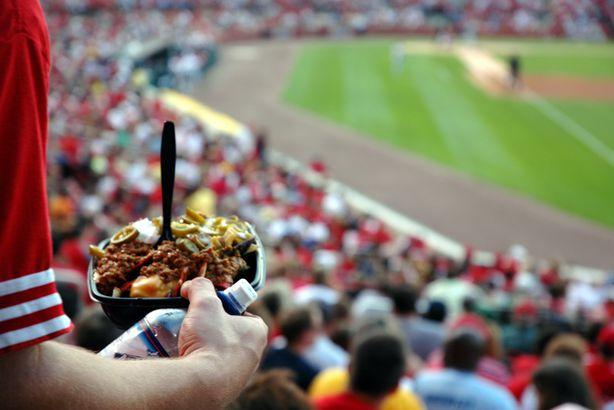 sports fan having nachos at a stadium during baseball game