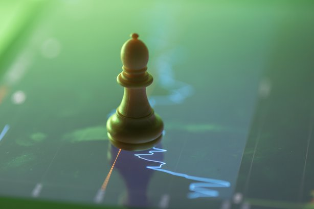 chess on the screen with stock chart