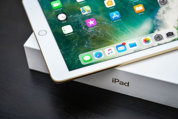 7th gen Apple iPad Gold with box on black wooden background closeup