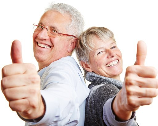 happy elderly senior couple holding their thumbs up