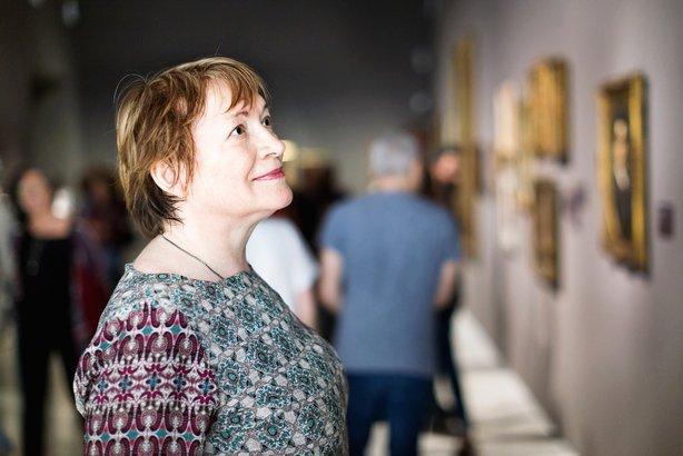 senior woman visiting museum and enjoying arts