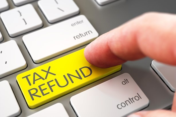 hand using laptop keyboard with tax refund yellow button