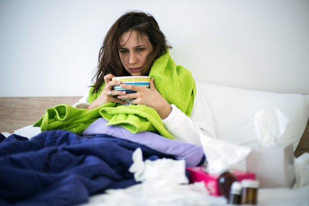 woman eating chicken noodle soup in bed while sick