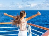 carefree woman looking at ocean with open arms in freedom pose