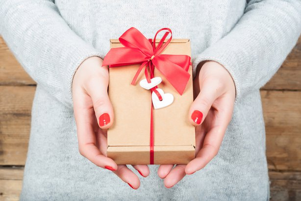 hands holding gift in kraft box on a wooden background