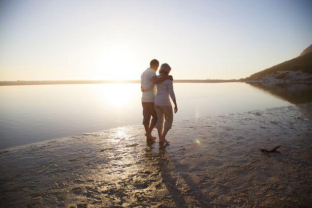 senior couple walking along a beach