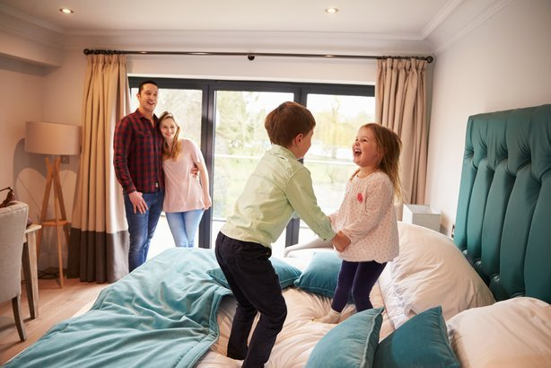 family on vacation with children playing on hotel bed