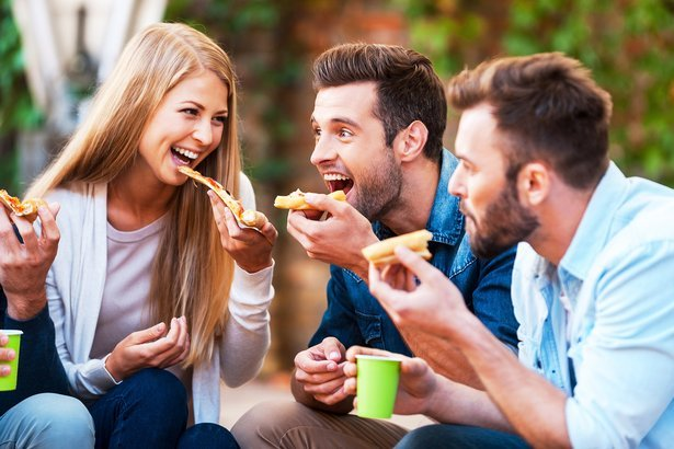 group of playful young people eating pizza while having fun together