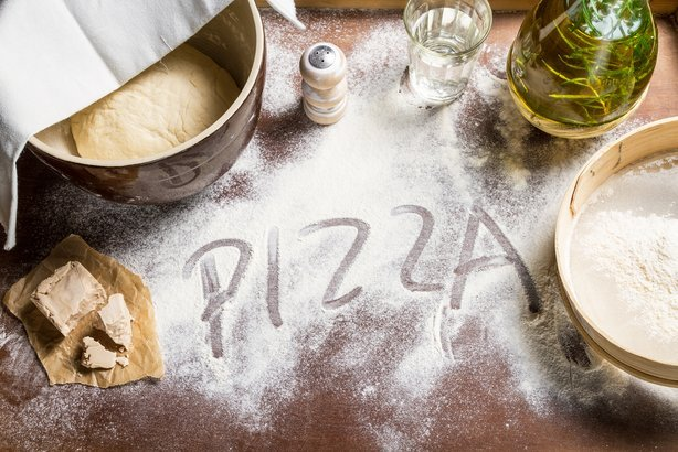 preparing dough for pizza with 'PIZZA' written in dough