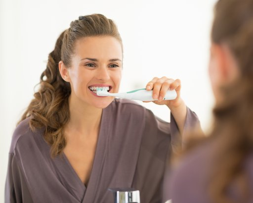 woman brushing teeth in bathroom