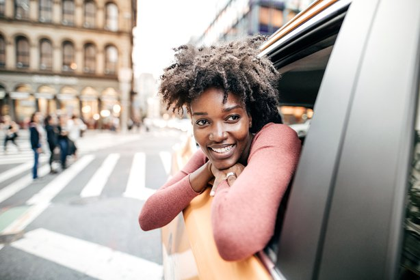 happy African American woman in taxi cab in New York City