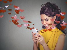 happy woman sending love text message on mobile phone with red hearts