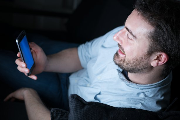 man looking at his mobile phone while sitting on couch