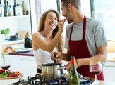 happy young couple cooking together in the kitchen at home