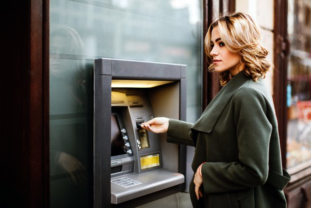 Woman looking cautious while using an atm in the city