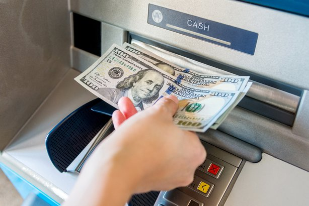 Hand taking money out of an ATM