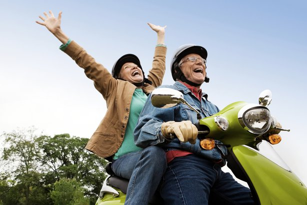 Senior couple riding on a scooter outside having fun