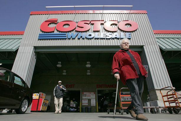Costco customers walk in front of a Costco Warehouse