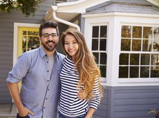 Happy young couple in front of their new house