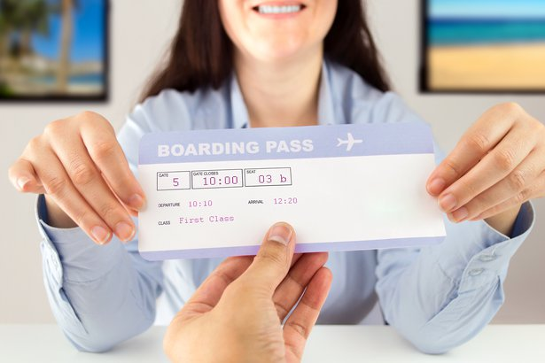 Woman handing a boarding pass to a customer