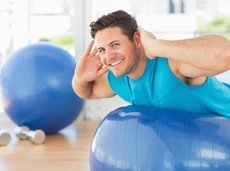 side view portrait of a young man exercising on fitness ball at a bright gym