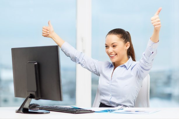 smiling businesswoman with computer and paper showing thumbs up