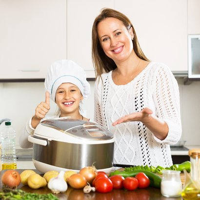 mother and smiling daughter to preparing dinner at in kitchen with a slow cooker
