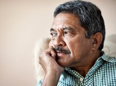 Older man looking emotional and staring at a window