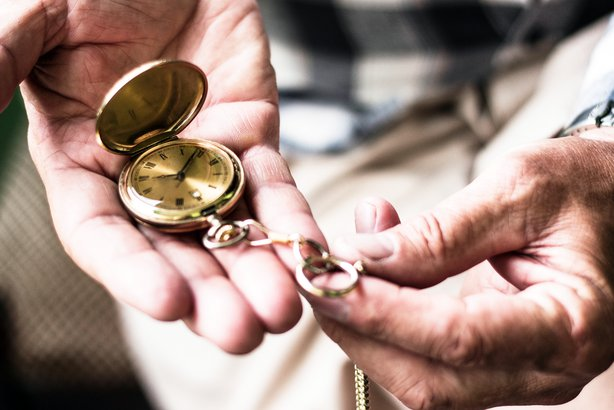 Old hands looking at a pocket watch